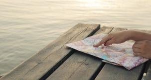La femme choisit l'itinéraire de son voyage à la carte sur la jetée de mer au coucher du soleil, plan rapproché de mains banque de vidéos