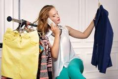 La femme choisit la veste dans le magasin photos stock