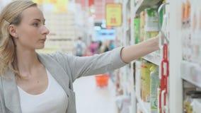 La femme choisit le jus dans le supermarché banque de vidéos