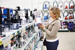 La femme choisit le mélangeur dans le magasin Photographie stock