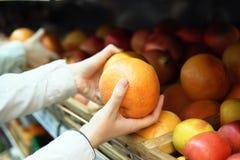 La femme choisit le pamplemousse dans le supermarché photographie stock libre de droits