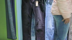 La femme choisit le pantalon dans le magasin banque de vidéos