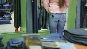La femme choisit le pantalon dans le magasin clips vidéos