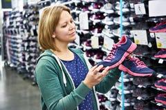 La femme choisit les chaussures de course dans le magasin Photo libre de droits