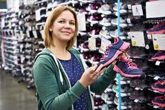 La femme choisit les chaussures de course dans le magasin Photographie stock