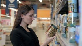 La femme choisit les olives en boîte l'épicerie, faisant des emplettes dans le supermarché de nourriture Photos stock