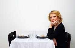 La femme célibataire s'assied sans compter que la table servie Photos stock