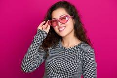 La femme cligne de l'oeil, beau portrait, posant sur le fond rose, les longs cheveux bouclés, lunettes de soleil dans la forme de Images libres de droits