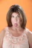 La femme colle la langue à l'extérieur Images stock