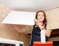 La femme colle la tuile de plafond images stock