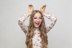 La femme comique en verres roses tenant des mains regardent le ` s comme l'oreille de lapin image libre de droits