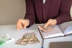 La femme comptable considère des dollars dans le lieu de travail Images stock