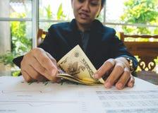 La femme compte l'argent avec le concept financier de papier de déclaration Images libres de droits