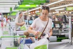 La femme compte sur le contrôle dans le supermarché photo libre de droits