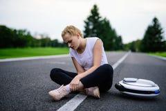 La femme conduisait le long du chemin de parc sur le monocycle et est tombée Il blesse Photos libres de droits