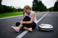 La femme conduisait le long du chemin de parc sur le monocycle et est tombée Il blesse Images libres de droits