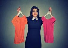 La femme confuse choisissant entre les robes et ne peut pas prendre la décision Image stock