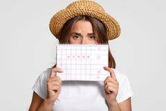 La femme contrariée tient le calendrier de perids, utilise le chapeau de paille, fait habiller l'expression de mécontentement, da photos libres de droits