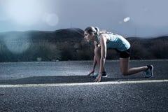 La femme convenable de sport de jeunes courant dehors sur la route goudronnée dans le paysage de montagne et la lumière dramatiqu Photos stock