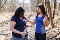 La femme convenable dissuadent son ami de poids excessif de prendre pi de régime Image stock