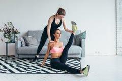 La femme convenable faisant l'étirage s'exerce avec l'aide de l'ami tenant sa jambe à la maison Photo stock