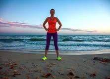 La femme convenable se tenant dans les sports embrayent sur la plage au coucher du soleil Photographie stock