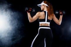 La femme convenable sportive, athlète avec des haltères font des exercices de forme physique sur le fond noir photographie stock