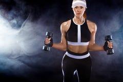 La femme convenable sportive, athlète avec des haltères font des exercices de forme physique sur le fond noir photo stock