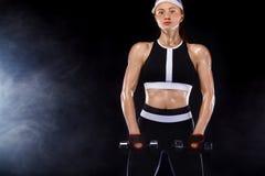 La femme convenable sportive, athlète avec des haltères font des exercices de forme physique sur le fond noir images libres de droits