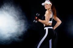 La femme convenable sportive, athlète avec des haltères font des exercices de forme physique sur le fond noir image stock