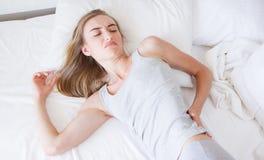 La femme coréenne et asiatique, douleurs de dos de fille et s'asseyent sur le lit dans la chambre à coucher pendant le matin, mau images stock