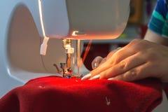 La femme coud la chaussette rouge de Noël Images stock