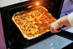 La femme a coupé avec une pizza faite maison de couteau en four électrique dans le ki Photographie stock libre de droits