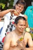 La femme a coupé des cheveux de l'homme pour soit ordonnée au nouveau moine photographie stock libre de droits