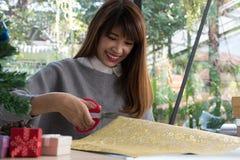 La femme a coupé le papier de cadeau avec des ciseaux pour envelopper la boîte actuelle de Noël Photographie stock