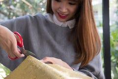 La femme a coupé le papier de cadeau avec des ciseaux pour envelopper la boîte actuelle de Noël Photos stock
