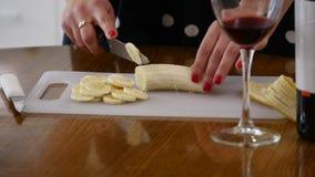 La femme coupe en tranches une banane sur un panneau en bois de cuisine dans une cuisine à la maison Faisant cuire la nourriture  banque de vidéos