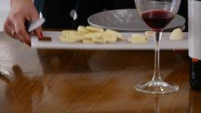 La femme coupe en tranches une banane sur un panneau en bois de cuisine dans une cuisine à la maison Faisant cuire la nourriture  clips vidéos