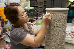 La femme coupe la décoration traditionnelle de motifs de tatouage au kaolin, Kuching, Malaisie Photographie stock