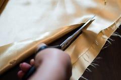 La femme coupe le tissu Image stock