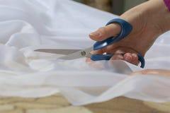 La femme coupe le tissu avec des ciseaux pour les rideaux de couture sur la fenêtre Le tissu se trouve sur le plancher Vue de côt Photos stock