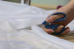 La femme coupe le tissu avec des ciseaux pour les rideaux de couture sur la fenêtre Le tissu se trouve sur le plancher Vue de côt Images stock