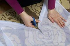 La femme coupe le tissu avec des ciseaux pour les rideaux de couture sur la fenêtre Le tissu se trouve sur le plancher Vue de ci- Photographie stock