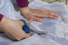 La femme coupe le tissu avec des ciseaux pour les rideaux de couture sur la fenêtre Le tissu se trouve sur le plancher Vue de ci- Image stock