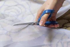 La femme coupe le tissu avec des ciseaux pour les rideaux de couture sur la fenêtre Le tissu se trouve sur le plancher Vue de ci- Photo libre de droits