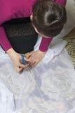 La femme coupe le tissu avec des ciseaux pour les rideaux de couture sur la fenêtre Le tissu se trouve sur le plancher Vue de ci- Photos stock