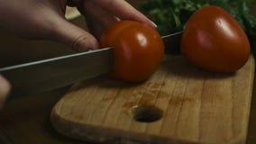 La femme coupe une tomate entière à deux grandes tranches d'un plat en bois, longueur en gros plan banque de vidéos