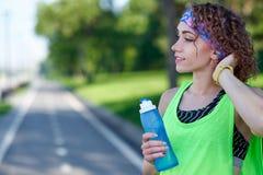 La femme courante a la coupure, eau potable pendant la course en parc d'été photographie stock libre de droits