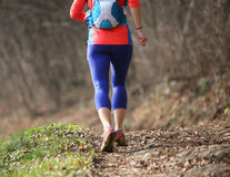 La femme court avec le costume de sport dans le photographe de traînée de montagne Photo libre de droits