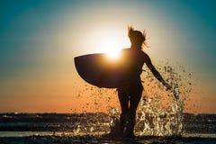 La femme court dans l'océan Photo stock